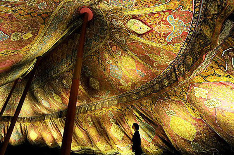 Image of richly decorated Ottoman tent interior as a precursor of the luxury embodied within modern glamping abodes